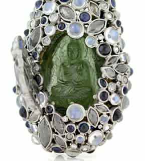 Todd Reed's piece was a Palladium and 22K yellow goldlocket featuring blue Moonstones, grey Diamonds, blue Sapphires and white Diamondsopening to reveal a 76.03 ct. Moldavite Buddha.Todd Reed's piece also won Best of Show.